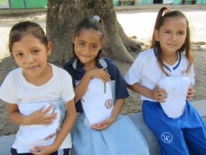 Luisa (center) receiving her new school uniform